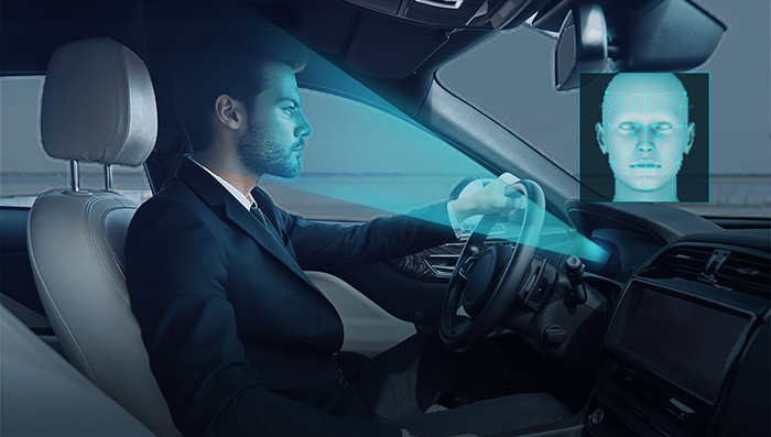 a driver in a car is being recognized and monitored by the car's driver monitoring system